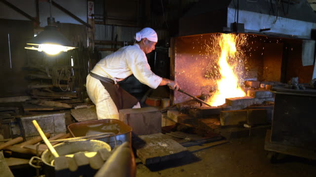 Blacksmith removing metal from furnace and using a hammer to shape it video