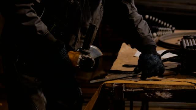 Blacksmith sawing metal with hand circular saw Professional blacksmith sawing metal with hand circular saw at forge, workshop. Handmade, craftsmanship and blacksmithing concept metalwork stock videos & royalty-free footage