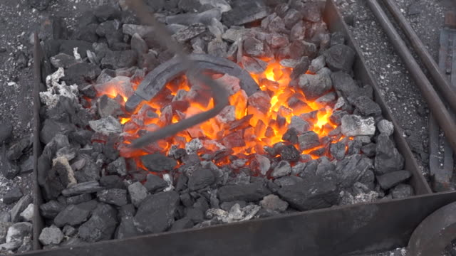 A blacksmith sets up a brazier heating flame with poker or fire iron for horseshoe heat-treating. A blacksmith sets up a brazier heating flame with poker or fire iron for horseshoe heat-treating. Flame and flying sparks flow of during rake up embers. wrought iron stock videos & royalty-free footage