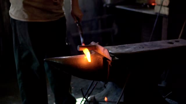 blacksmith shaping an iron with hammer - acciaio video stock e b–roll