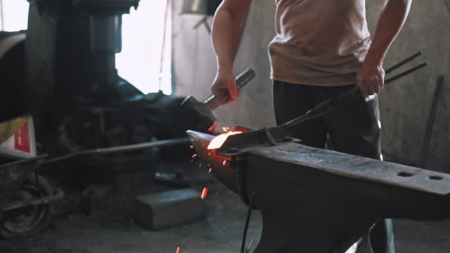 Blacksmith shaping metal on anvil Shot of blacksmith in his workshop in Malaysia. He is shaping peace of metal on anvil. wrought iron stock videos & royalty-free footage
