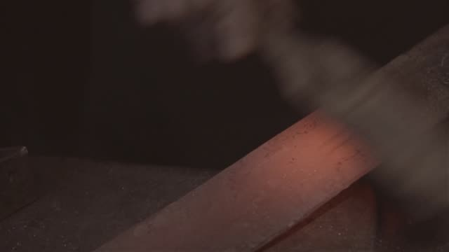 Blacksmith takes out a red-hot workpiece and beats it with a hammer