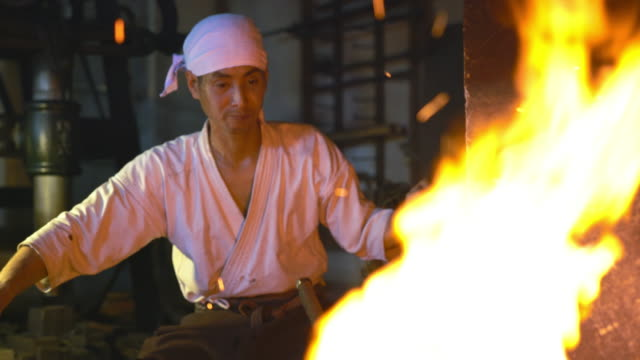 Blacksmith through the flames of his furnace Close up of a blacksmith through the flames as he pumps the bellows. Okayama, Japan. October 2016 blacksmith shop stock videos & royalty-free footage