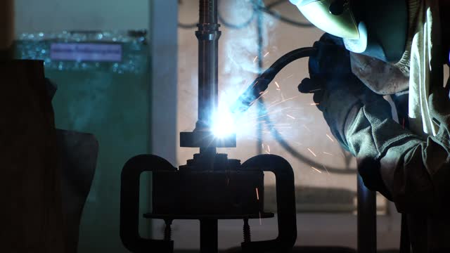 blacksmith welder in protective mask works with metal steel and iron using a welding machine. blacksmith welder in protective mask works with metal steel and iron using a welding machine. metal worker stock videos & royalty-free footage