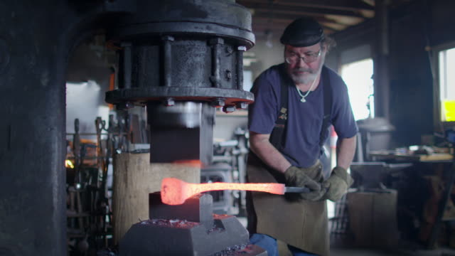 Blacksmith working hot iron with industrial hammer video