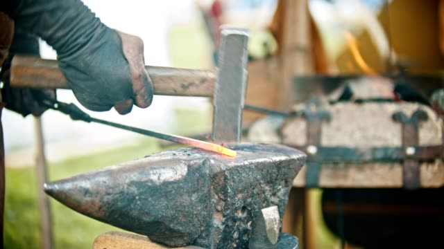Blacksmith working with an iron detail - hitting the hot metal with a hammer Blacksmith working with an iron detail - hitting the hot metal with a hammer. Mid shot metalwork stock videos & royalty-free footage