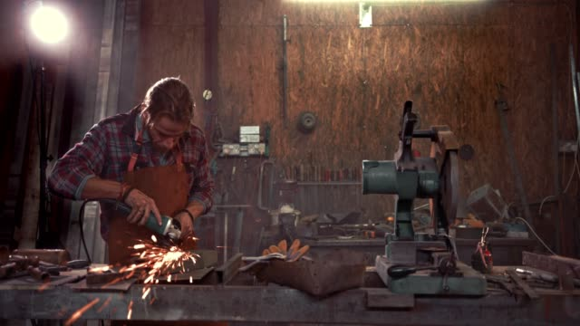 vídeos de stock e filmes b-roll de blacksmith working with angle grinder on workbench in industrial garage - moedor