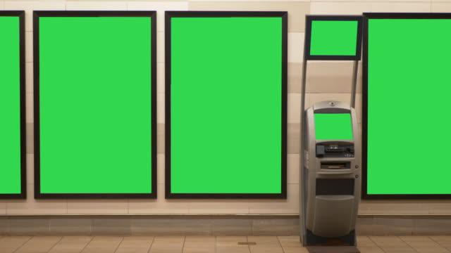 leere billboard anzeigen und atm geldautomaten schematisch in u-bahnstation - poster stock-videos und b-roll-filmmaterial