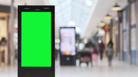 Blank electronic billboard in a shopping area A shopping arcade with electronic billboards and people out walking, blank billboard in front with green screen. advertisement stock videos & royalty-free footage