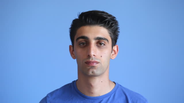 Blank facial expression of adult man on blue background video