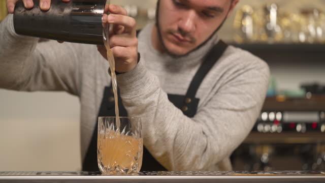 ein leeres glas, das auf der theke steht, und ein barkeeper nimmt den shaker von der theke und gießt grapefruit-saft hinein und legt eine grapefruit-scheibe auf den rand - tropischer cocktail stock-videos und b-roll-filmmaterial