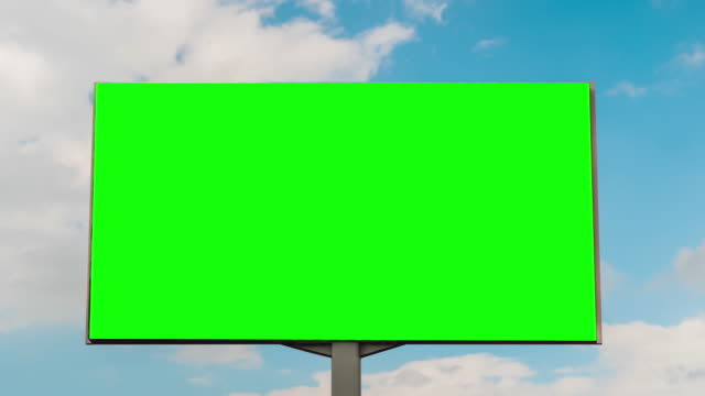 Blank green billboard and moving white clouds against blue sky - timelapse