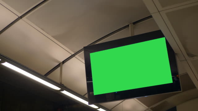 blank green screen flat screen monitor advertisement screen in train station - sottosuolo video stock e b–roll