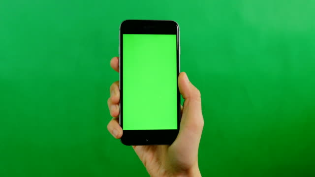 vídeos de stock e filmes b-roll de a blank green screen mobile phone on green background. - segurar