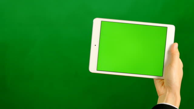 vídeos de stock e filmes b-roll de a blank green screen tablet on green background. - segurar