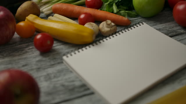 Blank notebook near cooking ingredients on wooden table