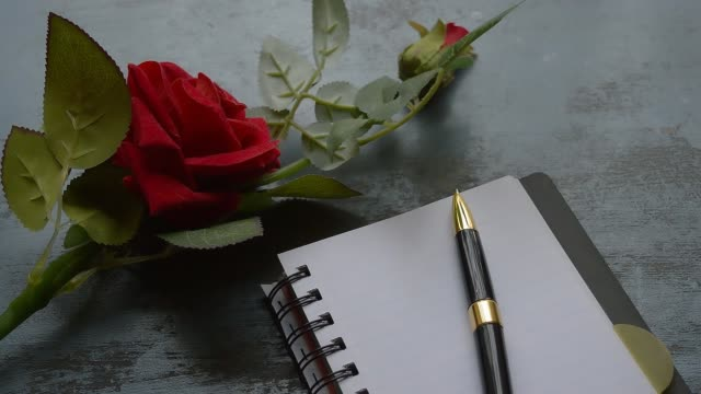 vídeos de stock e filmes b-roll de blank page notebook, pen and a beautiful red rose on rustic metal floor background with copy space. love letter writing proposal or propose concept for valentines day wedding and holidays. top view. - caneta