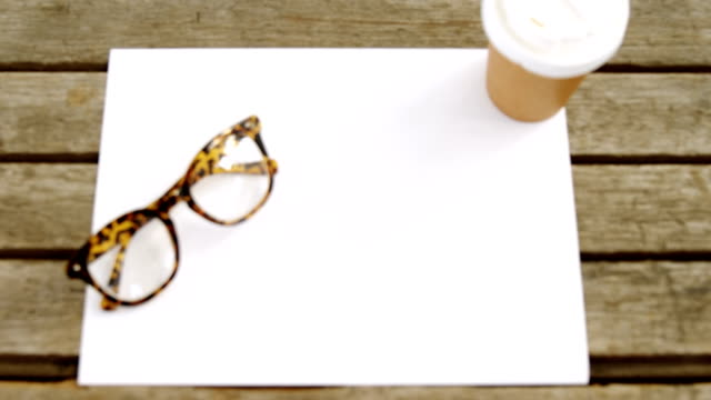 Blank paper with coffee and spectacles on wooden table 4k video