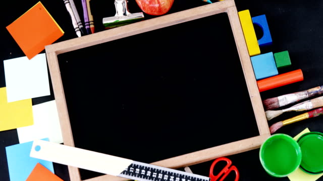 Blank slate surrounded by various school supplies video