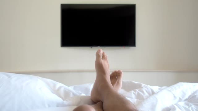 blank television on white wall in front of the bed. first person view from bed seeing men feet moving relax in front of TV. blank television on white wall in front of the bed. first person view from bed seeing men feet moving relax in front of TV. changing channels stock videos & royalty-free footage