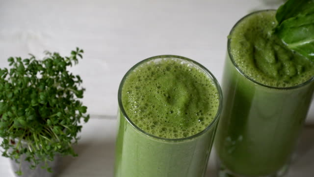 blended green smoothie with ingredients or cocktail on white background, breakfast vegan with a place for your text, concept of raw food detox - sedano video stock e b–roll