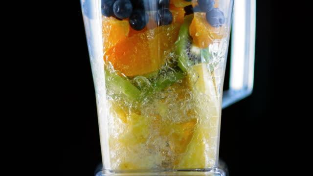vídeos y material grabado en eventos de stock de slo mo blender mezclando fruta sobre fondo negro - antioxidante