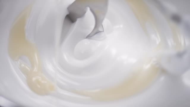 Blender whiskes white cream while beige liquid is added in the laboratory