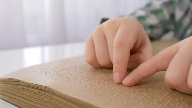 blind kid hands reading braille book with symbols font for visually impaired close up sitting at table - store filmów i materiałów b-roll