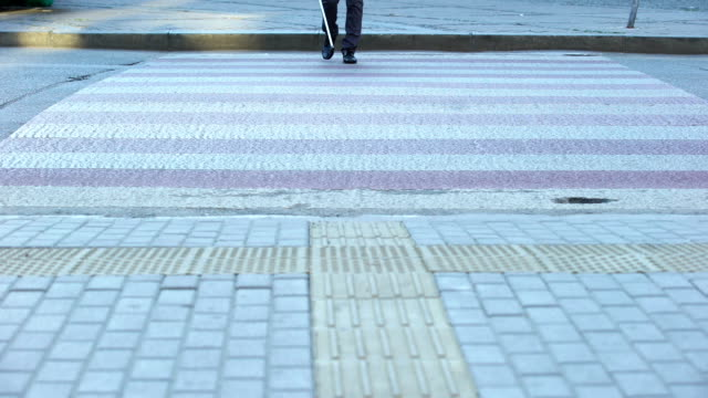 Blind male crossing street with white cane, using tactile tiles to navigate city