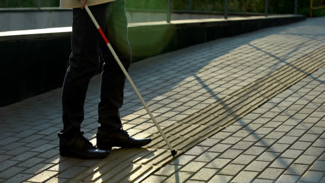 Blind male finding tactile paving with white cane, safely walking alone outdoors