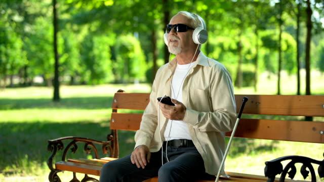 kör yaşlı adam kulaklıkları dinlerken sesli kitap dinleme, telefonda sesli mesaj - kulaklık seti ses ekipmanı stok videoları ve detay görüntü çekimi