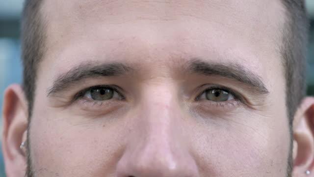 vídeos de stock e filmes b-roll de blinking eyes of young man - piscar