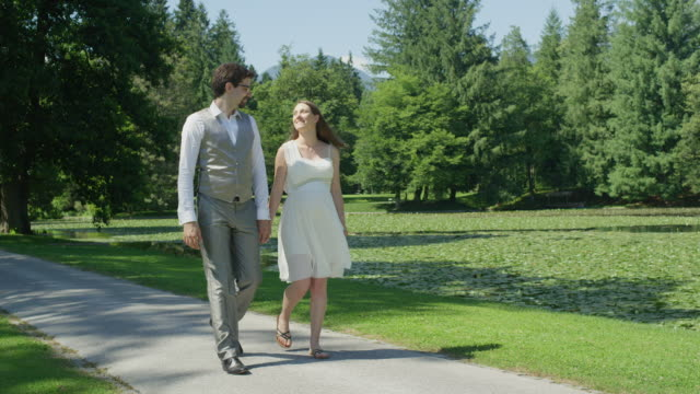 SLOW MOTION Blissful pregnant couple strolling through park on sunny summer day video