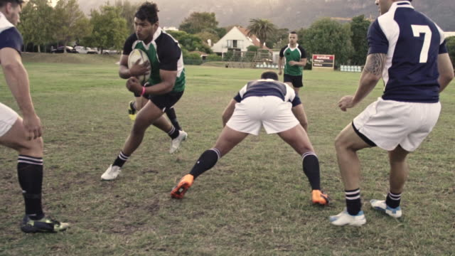 Blocking during a rugby game Rugby player tackling with the opponent during the match. Strong young men playing a game of rugby on the ground. rugby stock videos & royalty-free footage