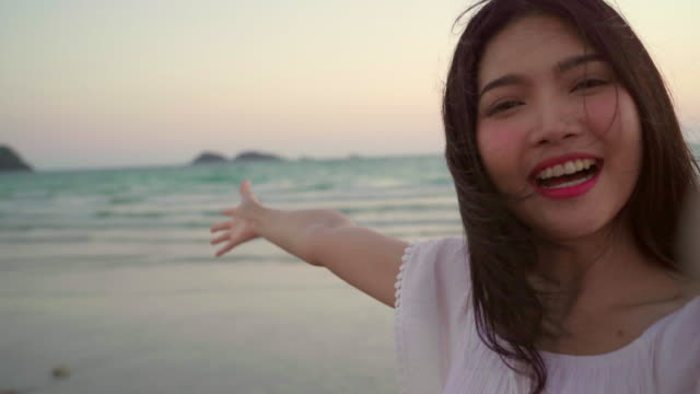 blogger asian woman record vlog video on beach, young beautiful female happy using mobile phone make vlog video on beach near sea when sunset in evening. lifestyle women travel on beach concept. - cultura tailandese video stock e b–roll