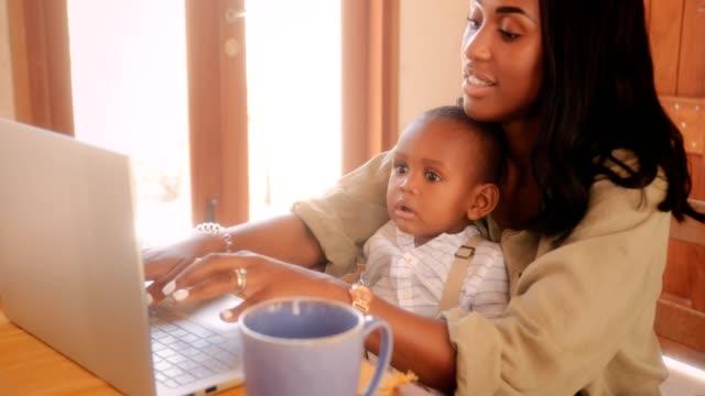 blogger mor med pojke som arbetar hemifrån på bärbar dator - working from home bildbanksvideor och videomaterial från bakom kulisserna