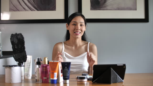 Blogger recording vlog video with makeup cosmetic at home online influencer on social media concept.live streaming viral