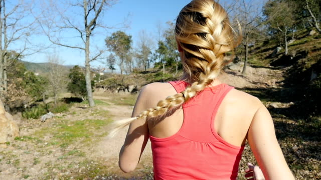 Blond athlete with braided hair jogging in nature video