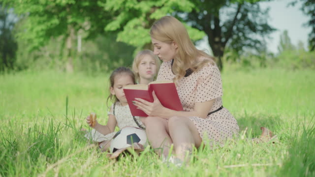 Blond Caucasian woman with tattoo on leg reading book on green meadow as little boy and girl sitting at back. Portrait of positive mother spending summer weekend with son and daughter Blond Caucasian woman with tattoo on leg reading book on green meadow as little boy and girl sitting at back. Portrait of positive mother spending summer weekend with son and daughter sister stock videos & royalty-free footage