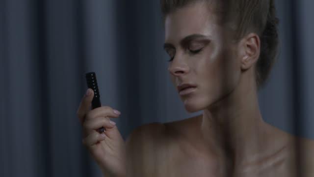 金髪ファッションモデルは、黒のアイライナーを処理します。ファッションのビデオ。 - グリースペイント点の映像素材/bロール