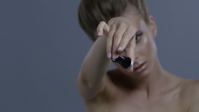金髪ファッションモデルは、黒のマニキュア液ボトルを処理します。ファッションのビデオ。 - グリースペイント点の映像素材/bロール