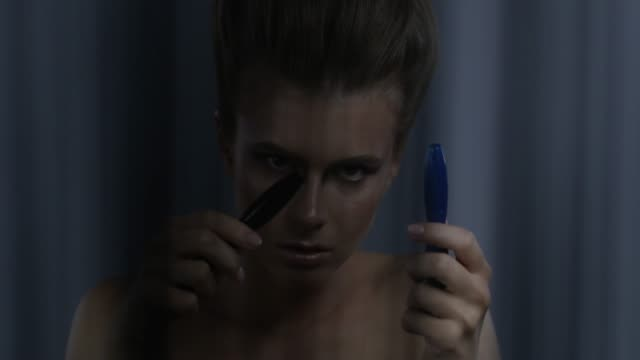 Blond fashion model holds 2 mascara tubes, hissing on them. Fashion video. Blond fashion model holds 2 mascara tubes, hissing on them, shows facial expressions. Fashion video. Slow Motion. 4K 30fps ProRes 4444 lip liner stock videos & royalty-free footage