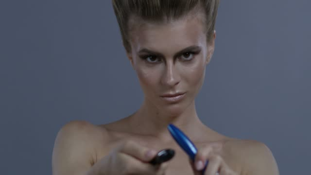 blond fashion model holds 2 mascara tubes, playing with them. fashion video. - clavicola video stock e b–roll