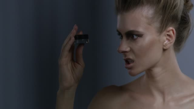 blond fashion model in stage make-up handles blue eyeshadow jar, hissing on it. fashion video. - гримировальные краски стоковые видео и кадры b-roll