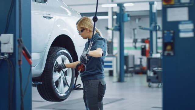 Blond Female Mechanic is Checing the Tire Pressure in a Wheel of a Vehicle. Empowering Woman Works in a Modern Clean Car Service. Specialists Inflates the Wheel After Fixing a Component on a Vehicle. video