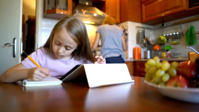 vidéos et rushes de fille blonde sur la tablette numérique et l'écriture dans son journal de navigation - agenda