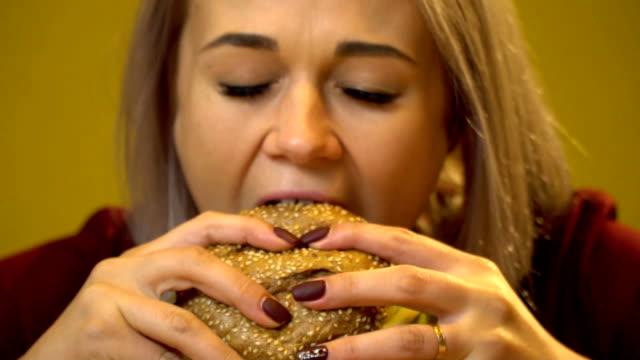 vídeos y material grabado en eventos de stock de rubia comiendo hamburguesa con carne y queso. de cerca. cámara lenta - hamburguesa