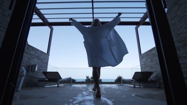 vidéos et rushes de une blonde dans un peignoir sort sur le balcon. vue de l'arrière. - peignoir