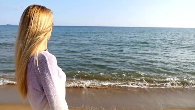 Blond girl looking at sea view video