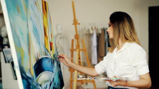 vidéos et rushes de peintre de fille blonde travaille en studio dépeignant le paysage de mer et bateau sur toile à l'aide de la brosse et tempera peintures regardant la photo et de profiter de son occupation. - toile à peindre